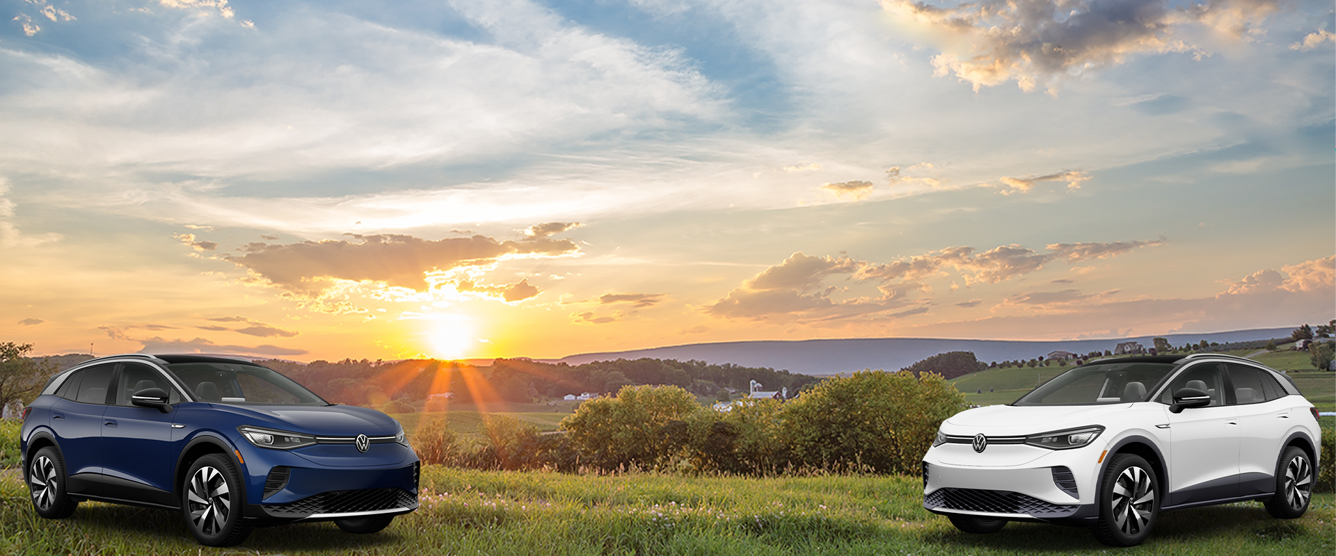2 Cars in a field during a sunset