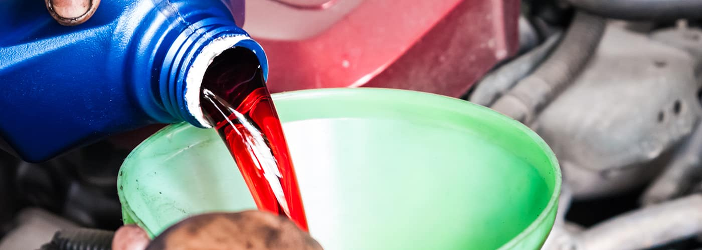 Hand pouring transmission fluid through funnel as for the good car maintenance