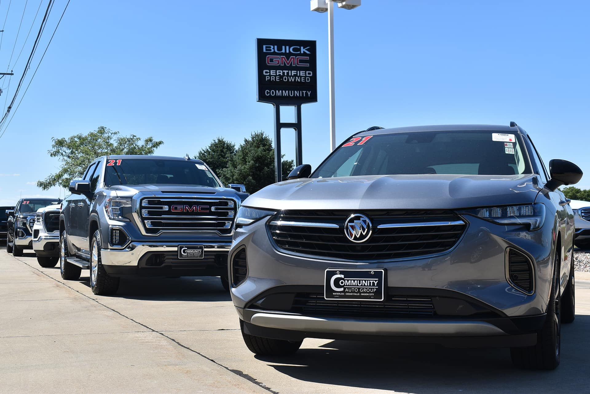 buick envision and gmc sierra in fron of dealership sign