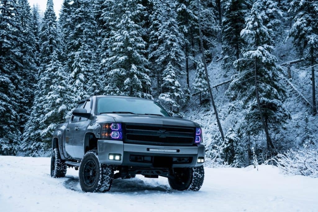 a chevy silverado in the snow with snow-covered evergreen trees behind it