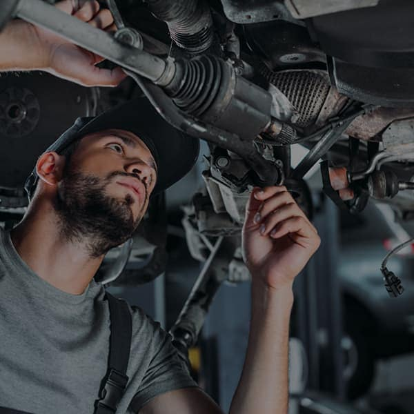 Service technician working underneath a vehicle