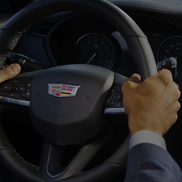 Two hands on a Cadillac steering wheel