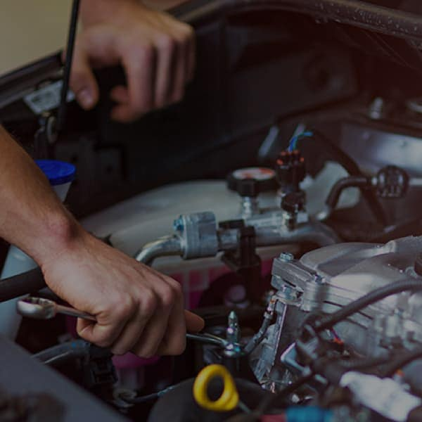 Service technicians hands working under the hood of a vehicle